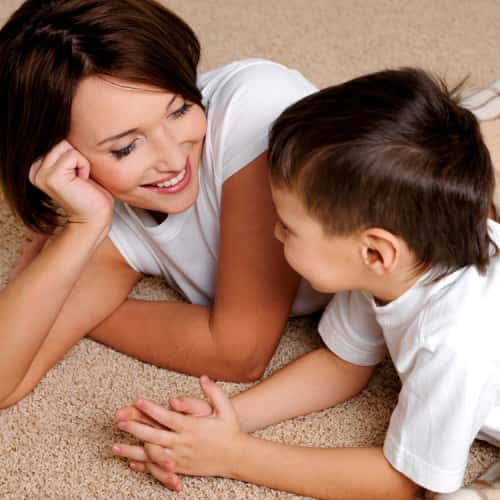 An image showing a young woman with a child playing on the floor