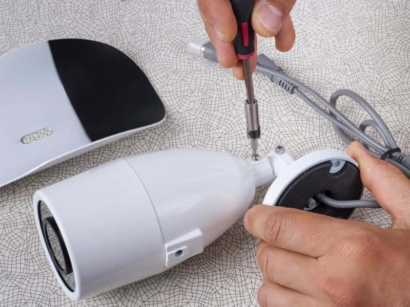 An image showing someone repairing a white faulty security camera.