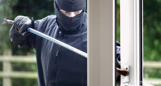 An image of a Burglar breaking into a house window with a crowbar