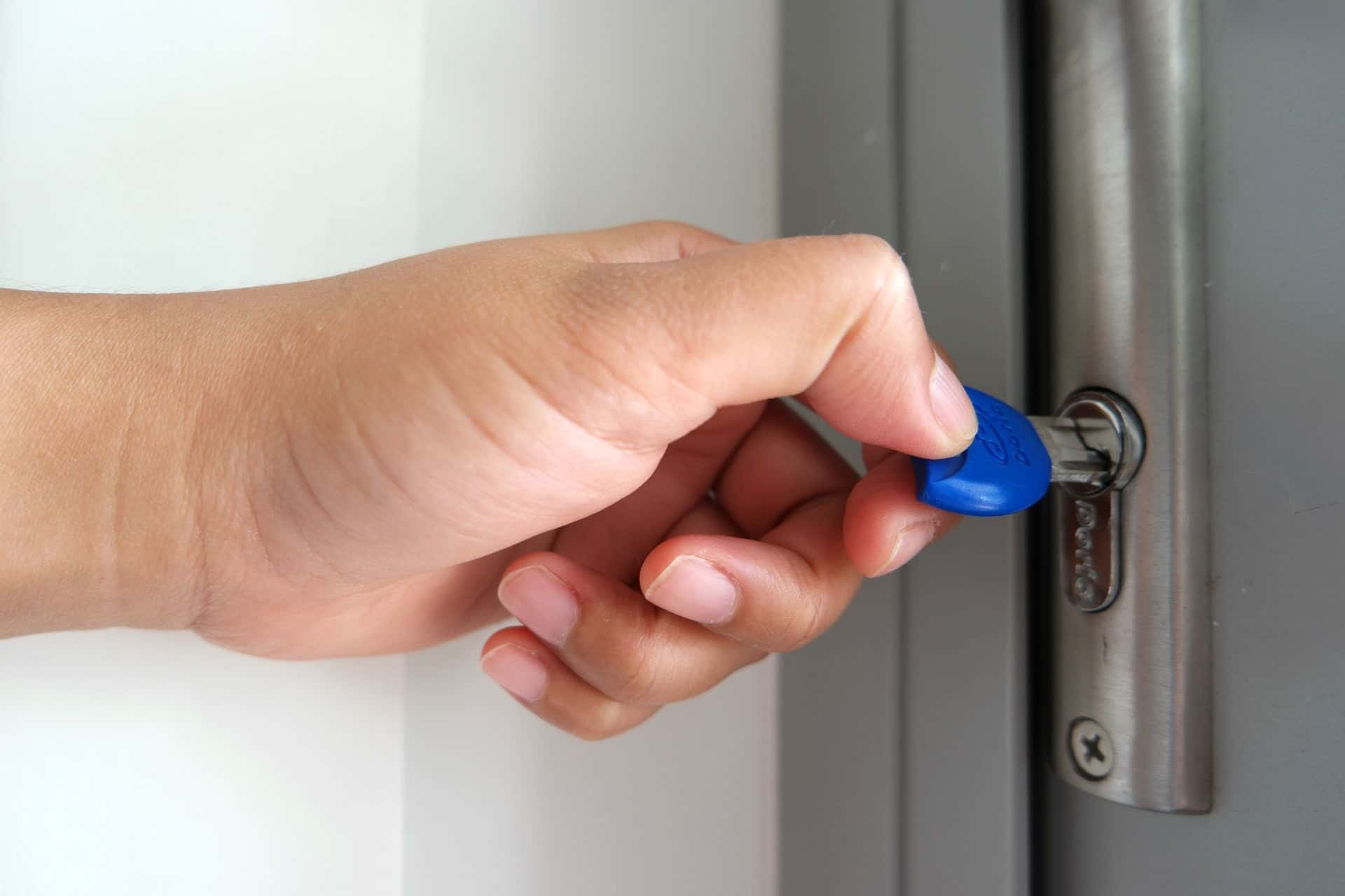 An image of a persona putting a key into a lock to enter a home.