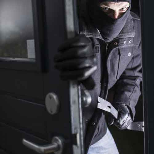 a burglar breaking into property using a crowbar.