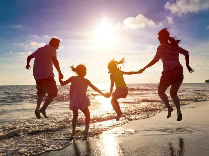 An image showing a family jumping on the sea front holding hands